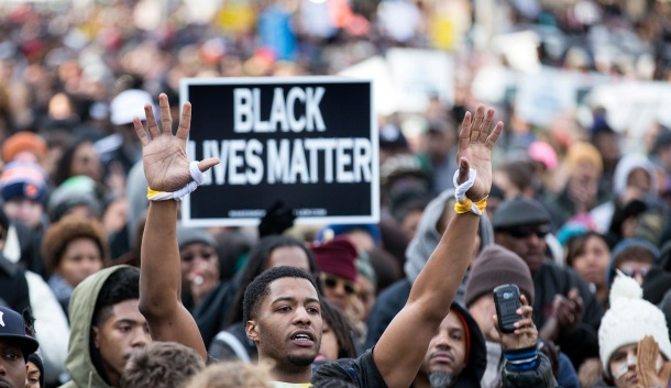 A man raises his arms at a rally during the National Action Network National March Against Police Violence in Washington